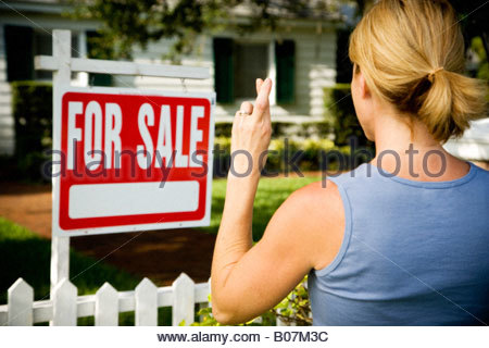 Woman standing by a for sale sign outside a family house, fingers crossed - Stock Photo