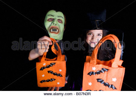 Children in costumes at a Halloween party, holding orange party bags - Stock Photo