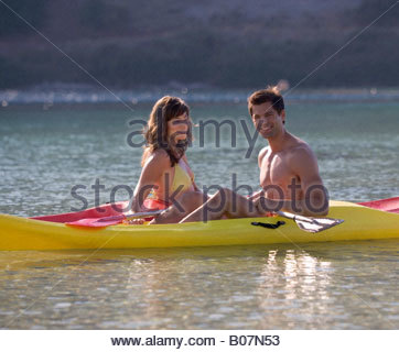 A couple canoeing on a lake - Stock Photo