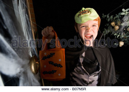 Boy in costume at a Halloween party, holding an orange party bag - Stock Photo