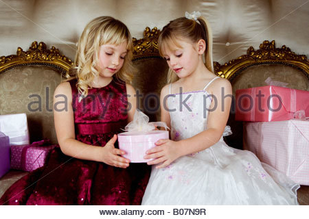 Little girls sharing birthday presents - Stock Photo