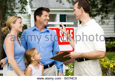 Family with estate agent outside property for sale - Stock Photo