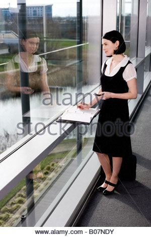 Businesswoman or secretary with an appointments diary, staring out of the window - Stock Photo