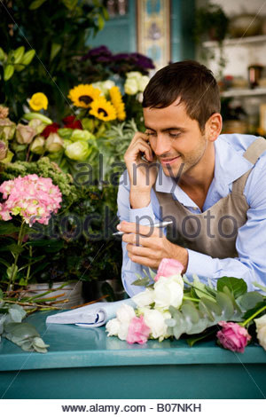 Male florist at the shop counter, taking an order over the telephone - Stock Photo