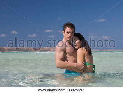 A couple standing in the sea - Stock Photo