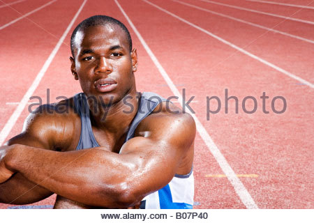 Portrait of a male athlete resting sitting on a running track - Stock Photo