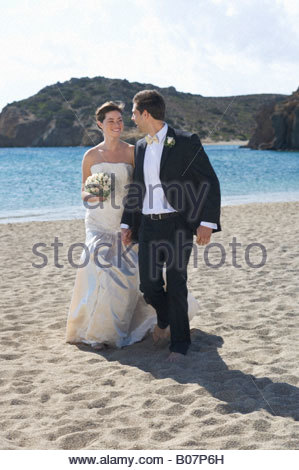 A bride and groom walking on a beach - Stock Photo