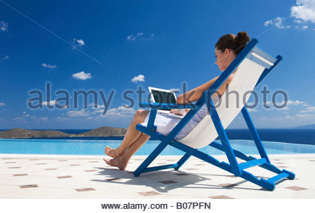 A woman sitting on a deck chair using a laptop - Stock Photo
