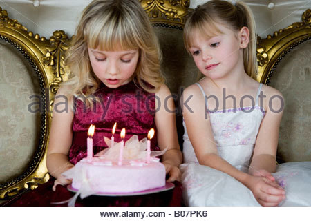 Little girl and friend holding a birthday cake with lit candles - Stock Photo