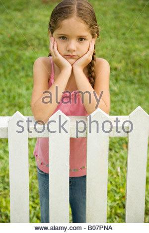 sad little girl leaning on fence - Stock Photo