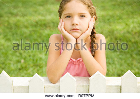 little girl leaning on fence looking sad - Stock Photo