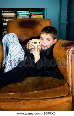 Little boy sitting in armchair with teddy bear - Stock Photo