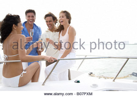 Two couples having drinks on board a luxury yacht - Stock Photo
