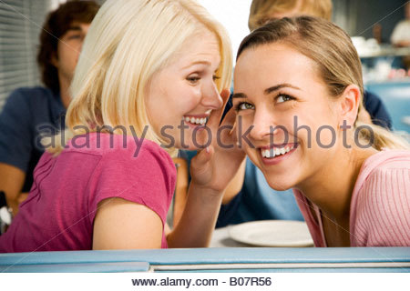 Portrait of smiling teenage girls with her friends in a diner - Stock Photo