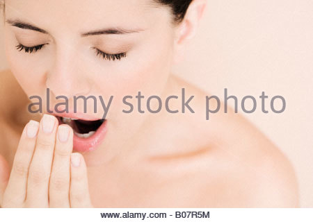 Portrait of young woman yawning - Stock Photo