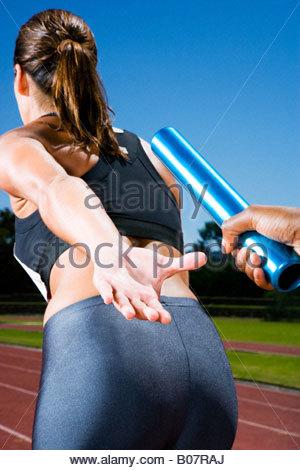 Baton passing between relay runners - Stock Photo