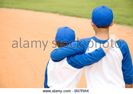 two boys walking away with arms around each other's shoulders - Stock Photo