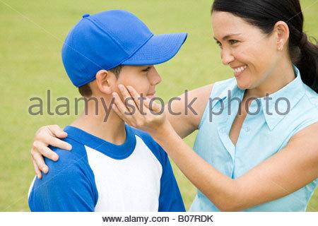 Mother congratulating son after baseball game - Stock Photo