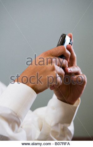Close up of a man using a mobile phone to SMS test message - Stock Photo