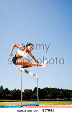 Female hurdler in action - Stock Photo