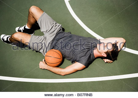 Man laying down on an outdoor basketball court - Stock Photo