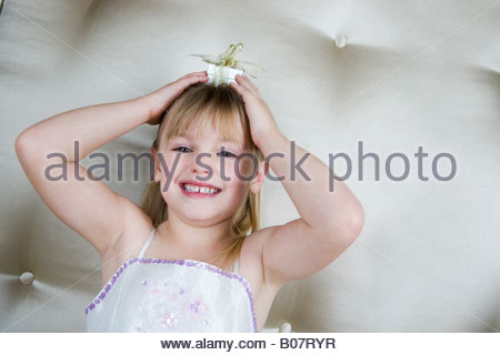 Little girl holding a present on top of her head - Stock Photo