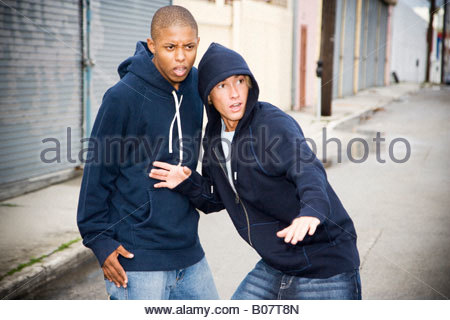 Portrait of two young street gang members looking suspicious - Stock Photo