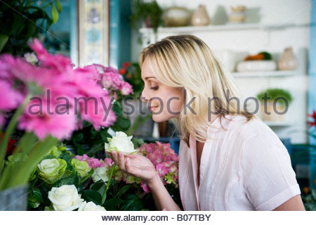 Woman in a florist's shop, smelling a white rose - Stock Photo