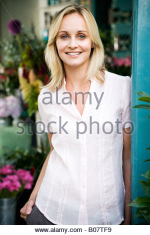 Woman florist standing at the entrance to her shop, smiling - Stock Photo