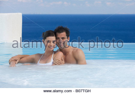 A couple relaxing in a jacuzzi - Stock Photo