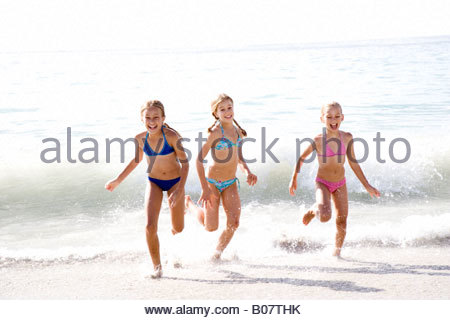 Three young girls running out of the sea - Stock Photo