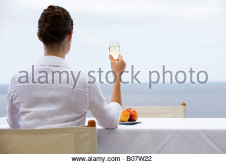 A woman drinking champagne alone - Stock Photo