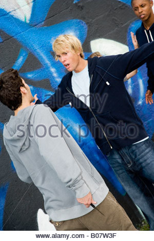 Confrontation between two young men  in front of a graffiti covered wall - Stock Photo