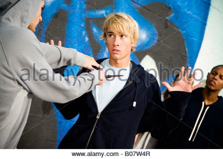 Confrontation between two young men and a group of friends in front of a graffiti covered wall - Stock Photo