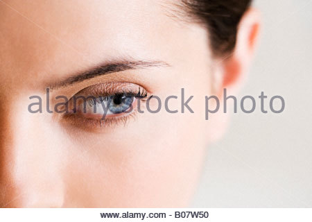Detail of woman's face showing left eye with blue iris - Stock Photo