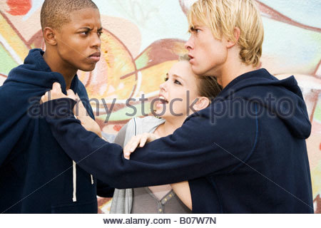 Two men fighting over a girl in front of a graffiti covered wall - Stock Photo