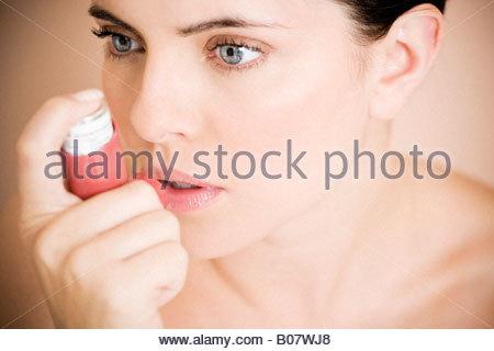 Female asthma sufferer using an inhaler - Stock Photo