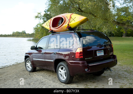 GMC Envoy Parked At Beach With Kayak On Roof Rack   Stock Photo