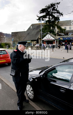 Traffic Warden at work in Bowness on Windermere Cumbria - Stock Photo