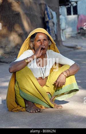 Old tribal woman smoking bidi, an Indian handmade cigarette made of tobacco or beedi leaves. Bhil tribe - Stock Photo