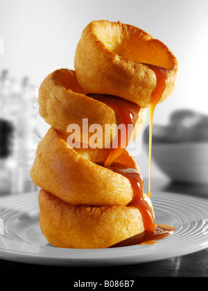 stack of yorkshire puddings and gravy in a table setting ready to eat - Stock Photo