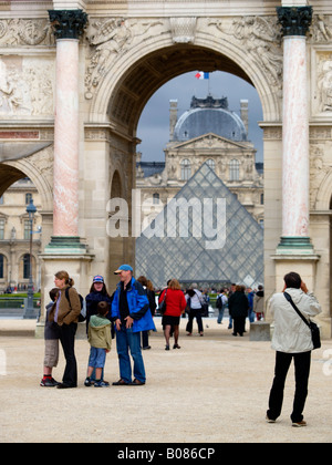 Tourists at the Louvre museum with the famous pyramid visible through an arch in the palace Paris France vertical - Stock Photo