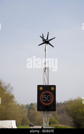 England UK Wind powered 50 mph speed sign illuminated by vehicle on country main road - Stock Photo