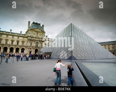The Pyramid by architect I M Pei at the Louvre museum in Paris France with queue at the museum entrance - Stock Photo