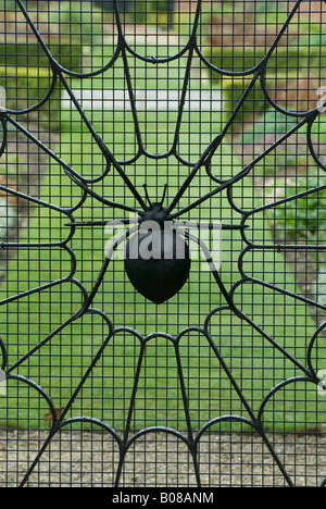 spiders web on wrought iron gate in garden - Stock Photo