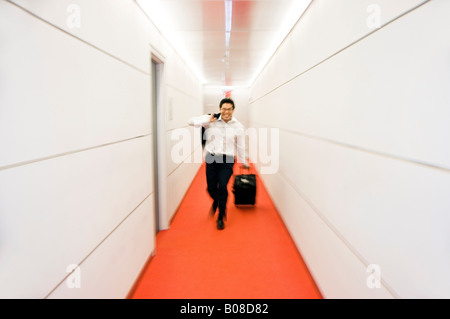 Businessman walking through hall with luggage - Stock Photo