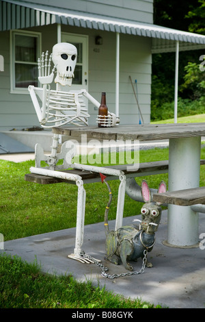 Welded folk art of skeleton holding a beer bottle with pet creature The Great Western Turnpike Route 20 Esperance - Stock Photo