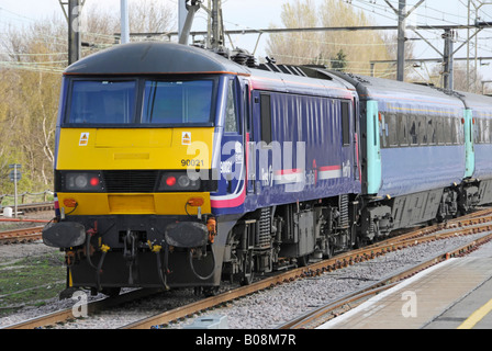 Rear end of National Express train departing station with loco logo showing as EWS - Stock Photo