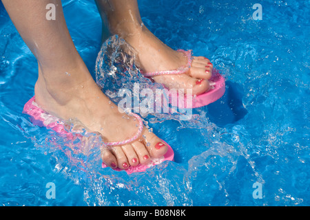 Feet wearing flip-flops in a paddling pool - Stock Photo