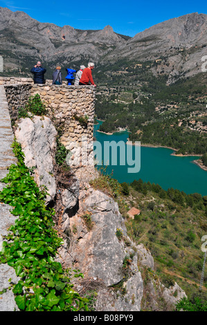 Tourists enjoying the view of mountains and reservoir dam from Castell de Guadalest, Guadalest, Costa Blanca, Spain - Stock Photo